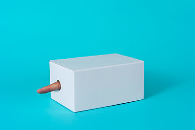 man's forefinger popping from a hole in a white cardboard box on a blue background - p1423m2076442 by JUAN MOYANO