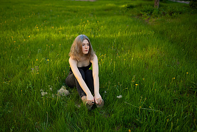 Young woman sitting in a meadow - p1646m2264263 by Slava Chistyakov