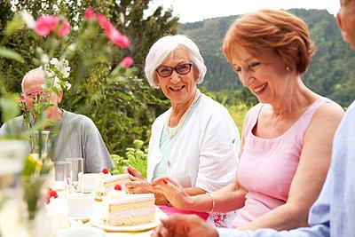 Senior ladies eating cake in garden - p300m1206154 by Michelle Fraikin