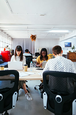 Colleagues working at desk in office - p300m2079203 by Bonninstudio