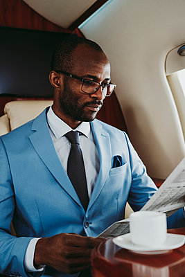 Young businessman reading newspaper while sitting in private jet - p300m2257045 by OneInchPunch