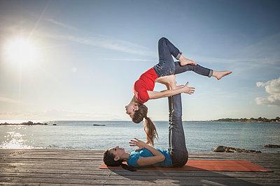 Women practising acro yoga at seaside - p429m2090965 by ROBERTO PERI