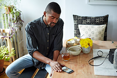 Black man using cell phone at table - p555m1409876 by Granger Wootz