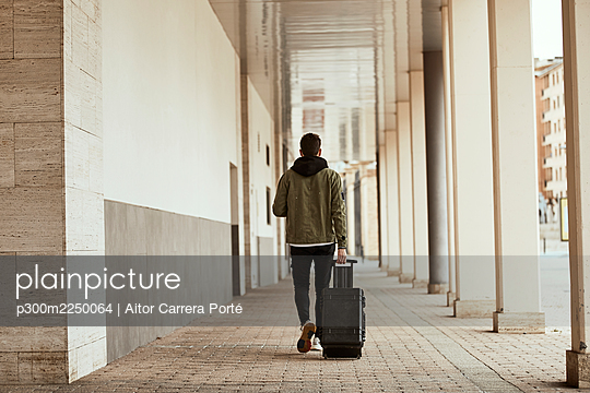 Man pulling suitcase while walking at arcade - p300m2250064 by Aitor Carrera Porté