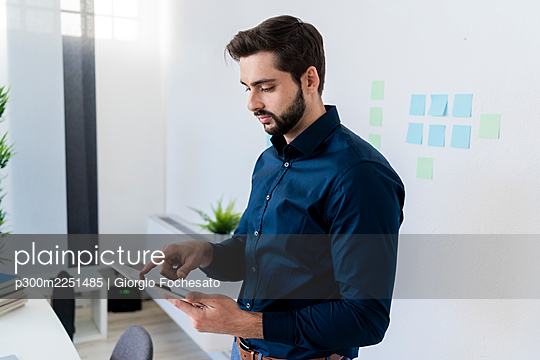 Male entrepreneur using digital tablet against wall in office - p300m2251485 by Giorgio Fochesato