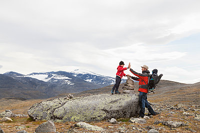 Man with sons high fiving over cairn in mountain landscape, Jotunheimen National Park, Lom, Oppland, Norway - p429m1561717 by Tiina & Geir