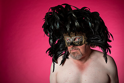 Shirtless man wearing a mask and feathers on his head  - p590m2015835 by Philippe Dureuil