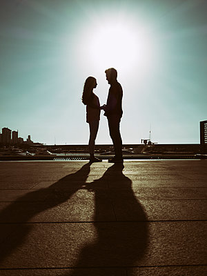 Silhouette of a young couple holding hands  - p794m1510966 by Mohamad Itani