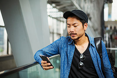 A man in a blue jacket in a modern building using his smart phone.  - p1100m1185881 by Mint Images