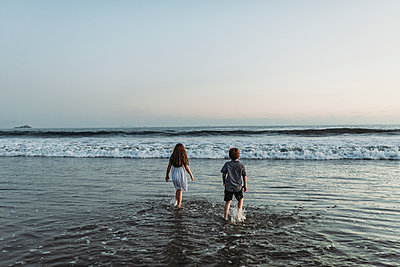 Siblings walking into the ocean staring at the horizon at sunset - p1166m2136539 by Cavan Images