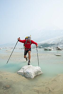 Backpacker leaps over stream onto boulder near glacier. - p1166m2153498 by Cavan Images