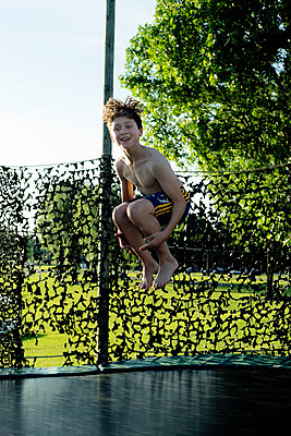 Junge auf dem Trampolin - p1212m1152960 von harry + lidy