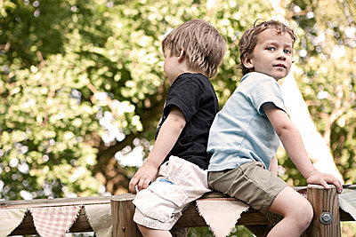 zwei Jungs sitzen auf Holzgerüst - p1230m1042626 von tommenz