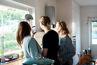 Woman taking selfie while standing with family in kitchen at new home - p426m1179586 by Maskot