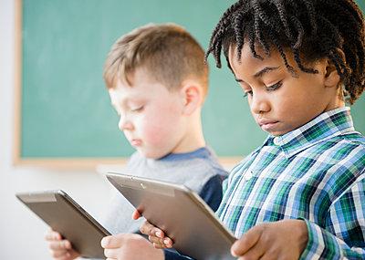 Students using digital tablet in classroom - p555m1410971 by JGI/Jamie Grill