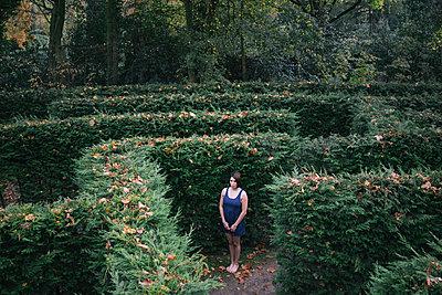 Junge Frau steht hilflos in einem Labyrinth - p586m957868 von Kniel Synnatzschke
