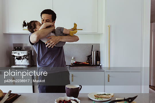 Father playing with son in kitchen at home - p426m2238917 by Maskot