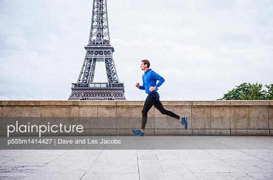 Caucasian man running near Eiffel Tower, Paris, France