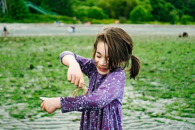 Cropped portrait of a young girl laughing while holding a crab - p1166m2289960 by Cavan Images