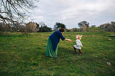 Little Girl Running Joyfully to Grandmother in Green Field - p1238m1042082 by Amanda Voelker