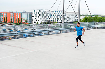 Man running on a parking level - p300m1587737 by Daniel Ingold