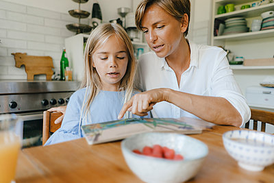 Mother and daughter reading book at table at home together - p300m2059192 by Kniel Synnatzschke
