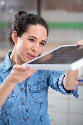 Businesswoman holding solar panel model at office - p300m2266013 by Florian Küttler