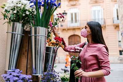 Female customer with face mask looking at flowers displayed - p300m2274944 by Ezequiel Giménez