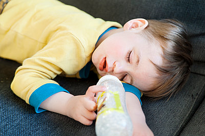 Boy sleeping with milk bottle - p312m1551979 by Johner Images