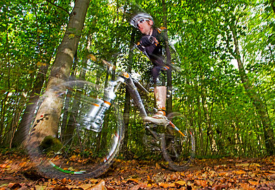 Mountain Bike rider..Single  rider racing through woodlands in Autumn/Fall during a cross country race.Forest of Dean,UK - p343m1026687 by James Silverthorne