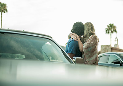 Young couple, standing beside car, hugging, looking away - p429m1547841 by Seb Oliver