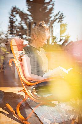Junge Frau liest ein Buch im Schaukelstuhl zuhause - p741m2176780 von Christof Mattes