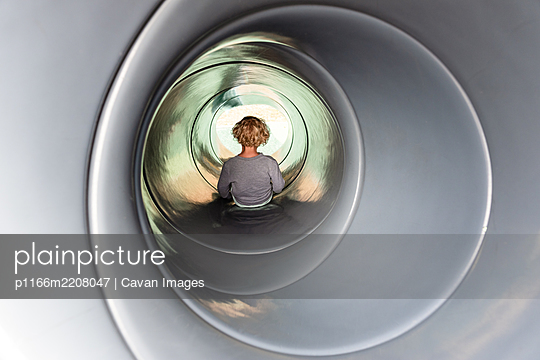 Young curly haired child in a tube slide at a playground park - p1166m2208047 by Cavan Images