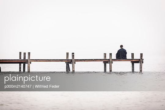 Back view of man sitting on jetty at Lake Starnberg, Germany - p300m2140747 by Wilfried Feder