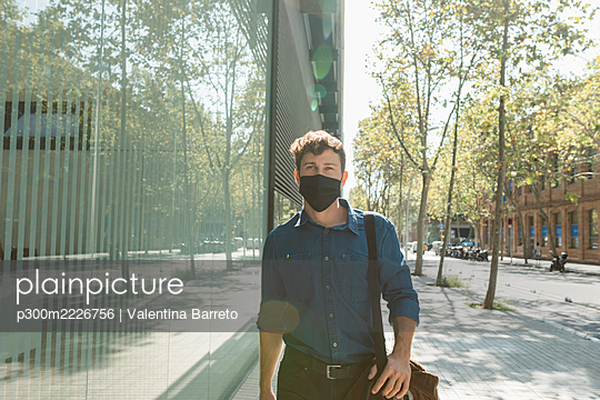 Young businessman wearing face mask while walking on footpath in city during coronavirus crisis - p300m2226756 by Valentina Barreto
