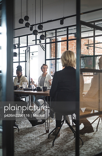 Female entrepreneur discussing with colleagues seen through doorway of startup company - p426m2296116 by Maskot