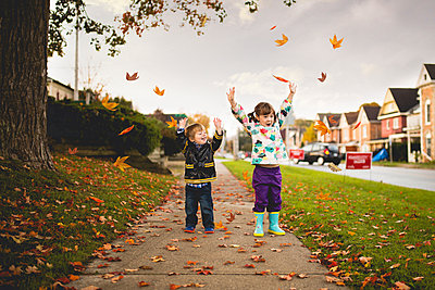 Cheerful siblings with arms raised on footpath during autumn - p1166m1182633 by Cavan Images