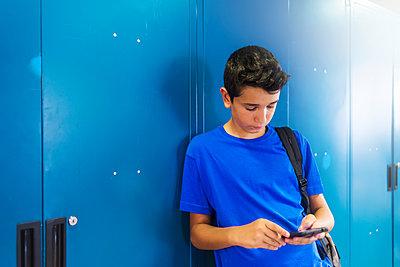 Schoolboy using smart phone while standing against locker in school - p1166m2033697 by Cavan Images