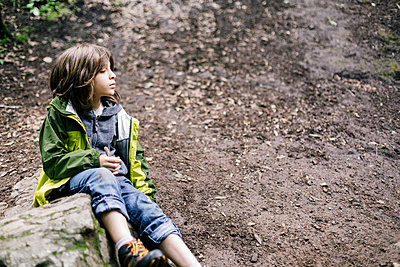 Close up side view boy sitting over moss rock looking away - p1166m2214705 by Cavan Images