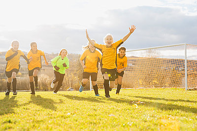 Successful soccer players running on field - p1192m1043699f by Hero Images