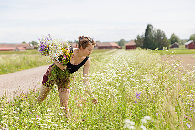 Sweden, Dalarna, Mora, Mid adult woman with bunch of wildflowers - p352m1349318 by Gustaf Emanuelsson