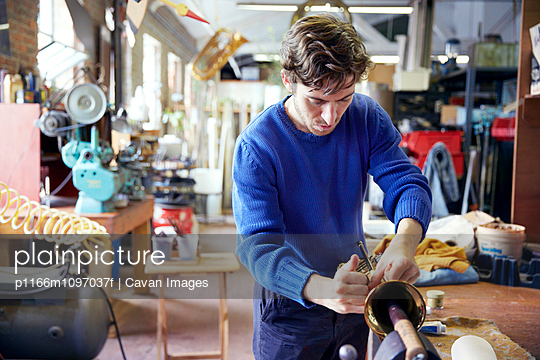 Man manufacturing trumpet while working in workshop - p1166m1097037f by Cavan Images