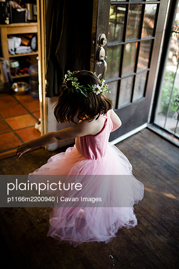 Young girl spinning by front door wearing tutu and flower crown - p1166m2200940 by Cavan Images