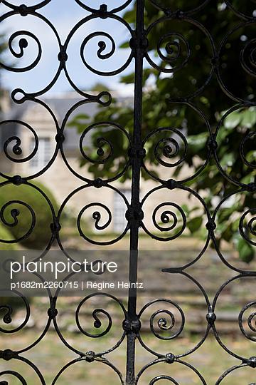 House seen through a wrought iron gate - p1682m2260715 by Régine Heintz