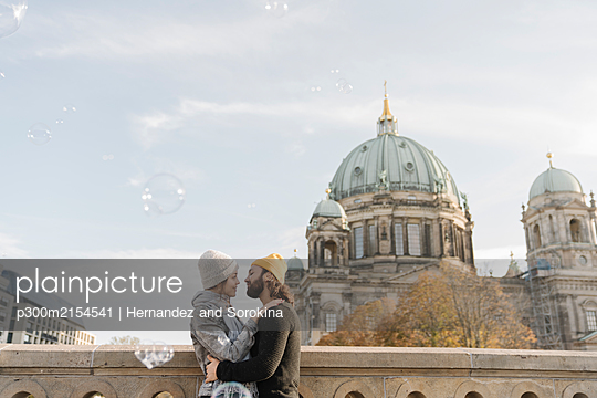 Young couple embracing with Berlin Cathedral in background, Berlin, Germany - p300m2154541 by Hernandez and Sorokina