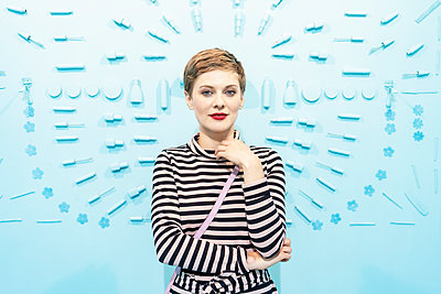 Woman in front of light blue background with beauty cosmetic articles  - p1332m2055046 by Tamboly