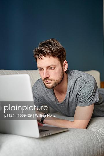 Junger Mann mit Laptop auf dem Sofa - p1124m1589429 von Willing-Holtz