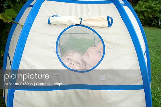 Geschwister im Zelt in Garten - p1311m2013906 von Stefanie Lange