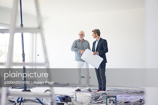 Man in suit and senior man talking on room under construction - p300m2004080 von Robijn Page