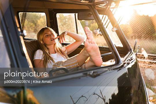 Young woman sitting in a van with feet up - p300m2023974 by Kike Arnaiz
